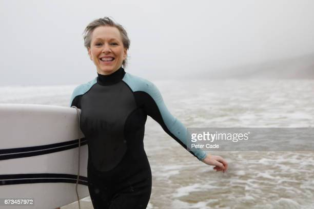 Older woman running out of sea with surfboard