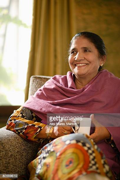 older woman sitting on couch, holding tea