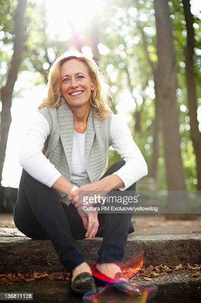 Older woman sitting on park steps