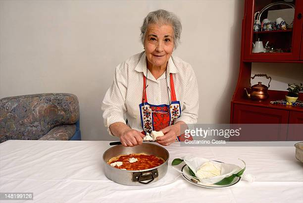 Older woman slicing cheese for pizza