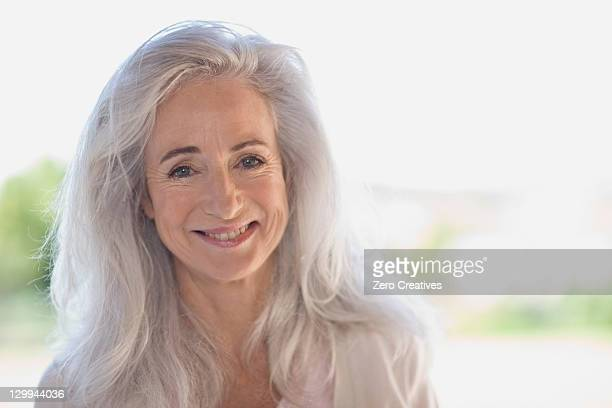 older woman smiling outdoors - long hair stock pictures, royalty-free photos & images