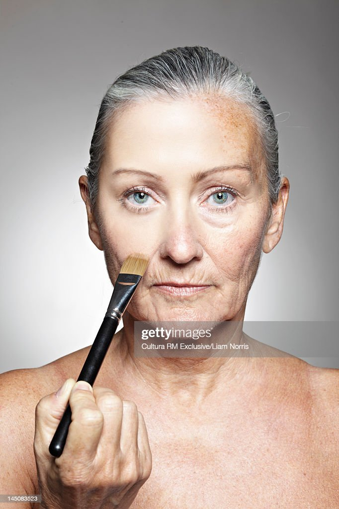 Older woman smoothing her face : Stock Photo