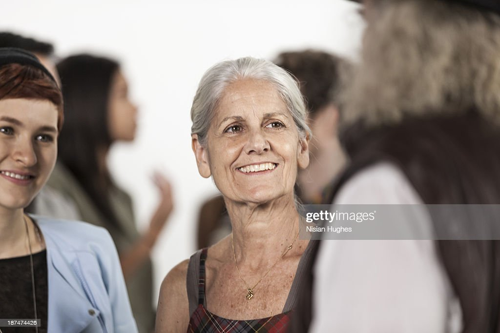 older woman standing in crowd of people : Foto stock