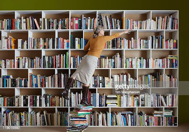 Older woman standing on stack of books