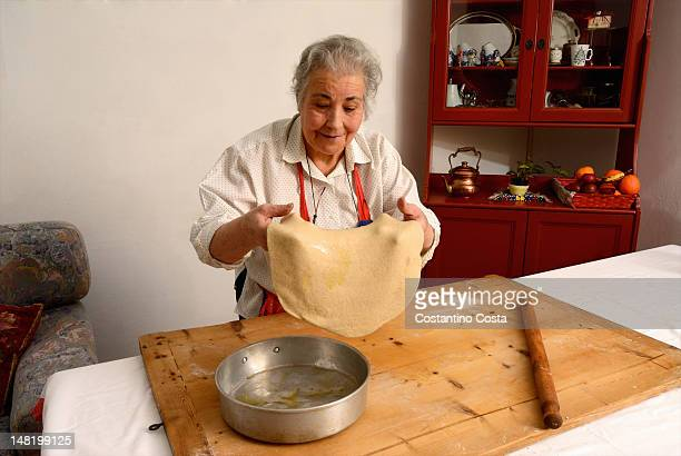 Older woman stretching sheet of dough