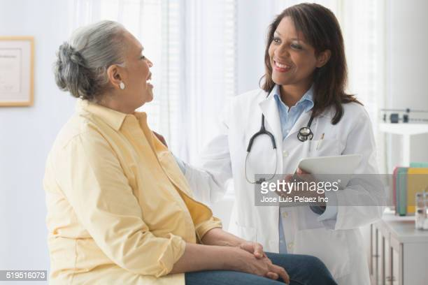 older woman talking to doctor in office - female doctor stock photos and pictures