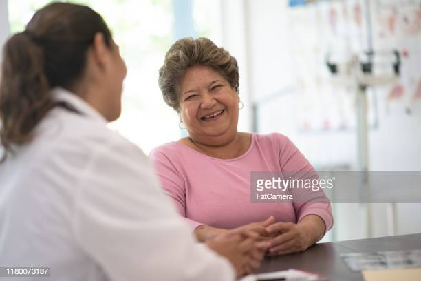 older woman talking with the doctor stock photo - fatcamera stock pictures, royalty-free photos & images