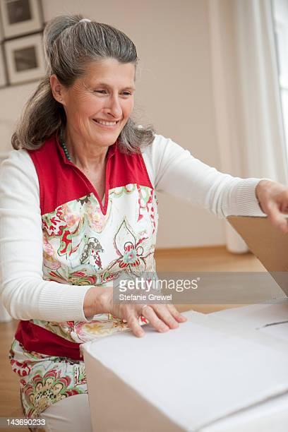 older woman unpacking box - stefanie grewel stock-fotos und bilder