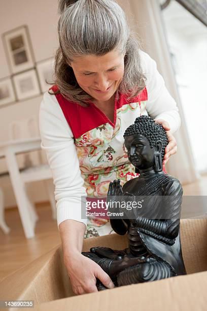older woman unpacking buddha statue - stefanie grewel stock-fotos und bilder