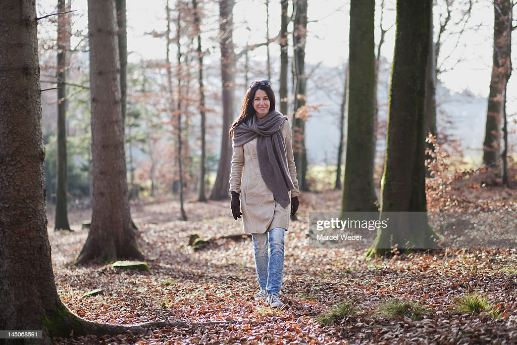 Older woman walking in forest : Stock Photo
