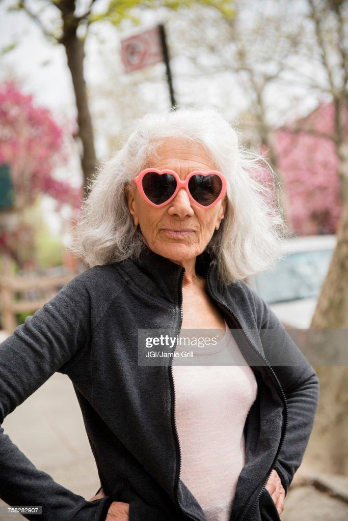 Older woman wearing heart-shape sunglasses : Stock Photo