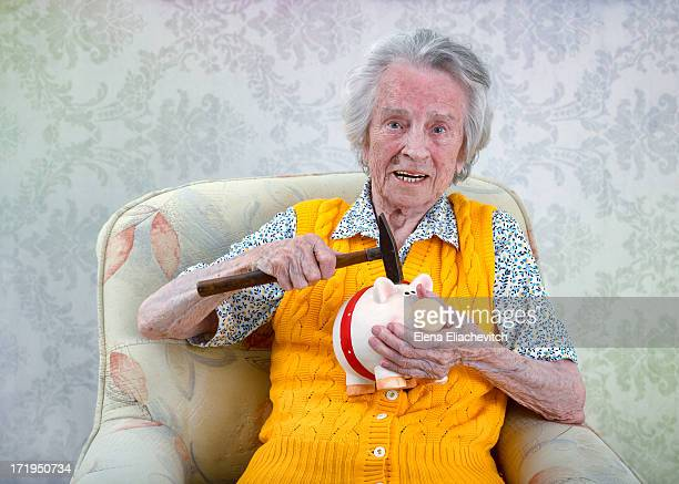 Older woman with a hammer and a piggy bank