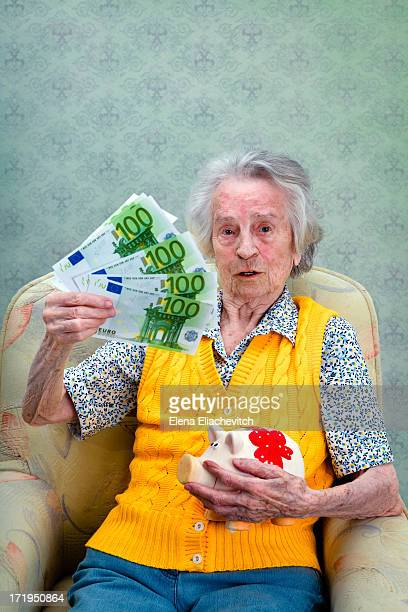 Older woman with a piggy bank and  banknotes