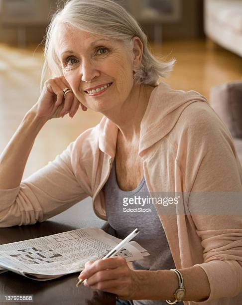 Older woman with newspaper crossword puzzle