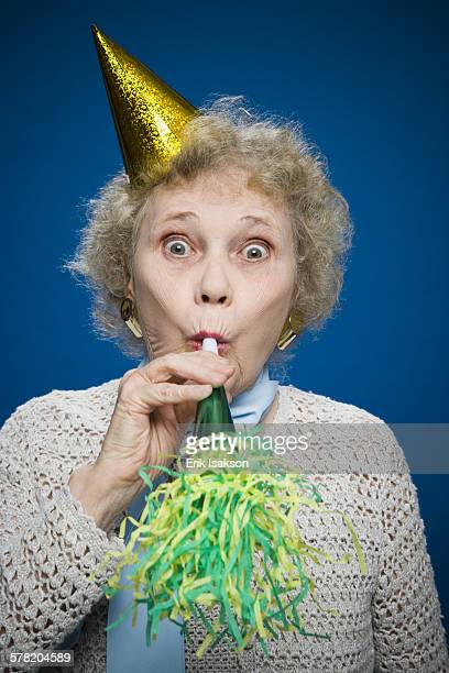 Older woman with noisemaker and party hat