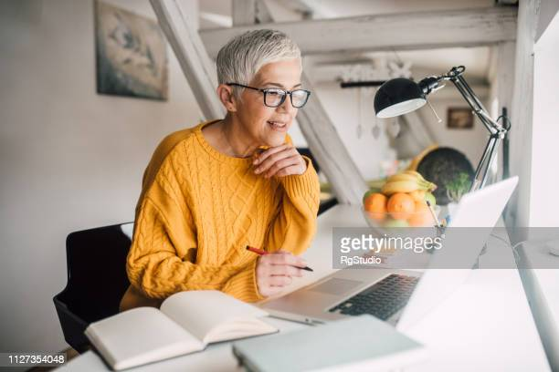 older woman working on laptop - online class stock pictures, royalty-free photos & images