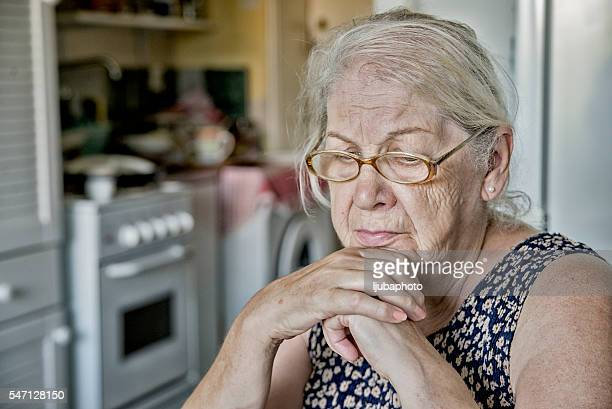 Older woman worried about the future -  praying old woman