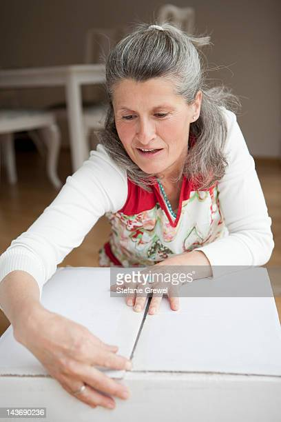 Older woman wrapping cardboard box