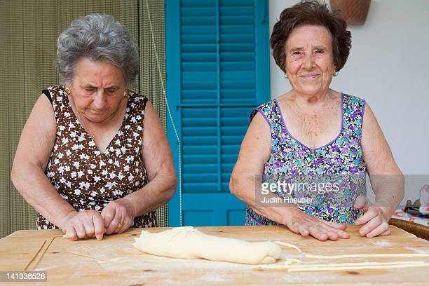 older women making pasta together - cultura italiana foto e immagini stock