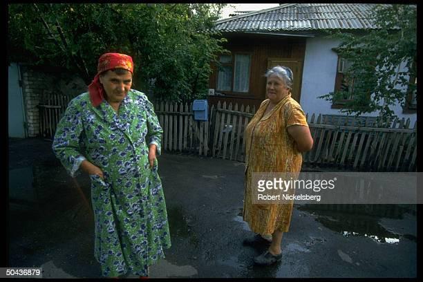 2 older women outside mailbox on picket fencequaint home in Central Steppes region peopled by Kazakhs Russians Ukrainians prob Ekibastuz