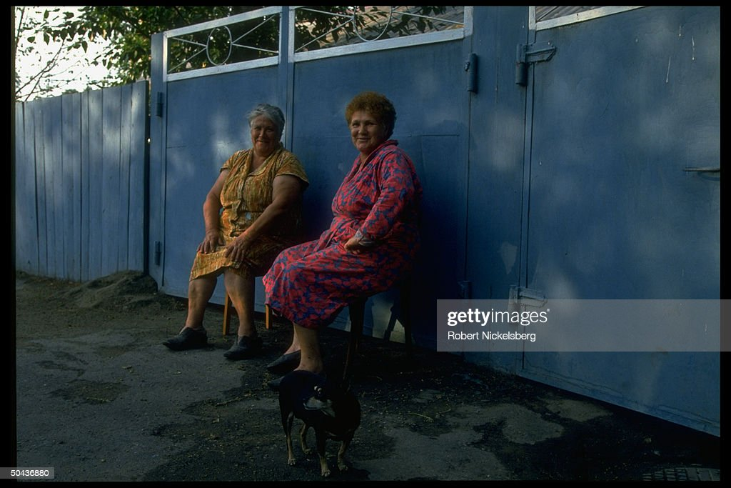2 older women sitting, chatting outside : News Photo