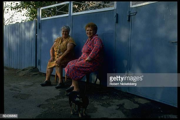 2 older women sitting chatting outside fence in Central Steppes region peopled by Kazakhs Russians Ukrainians prob Ekibastuz
