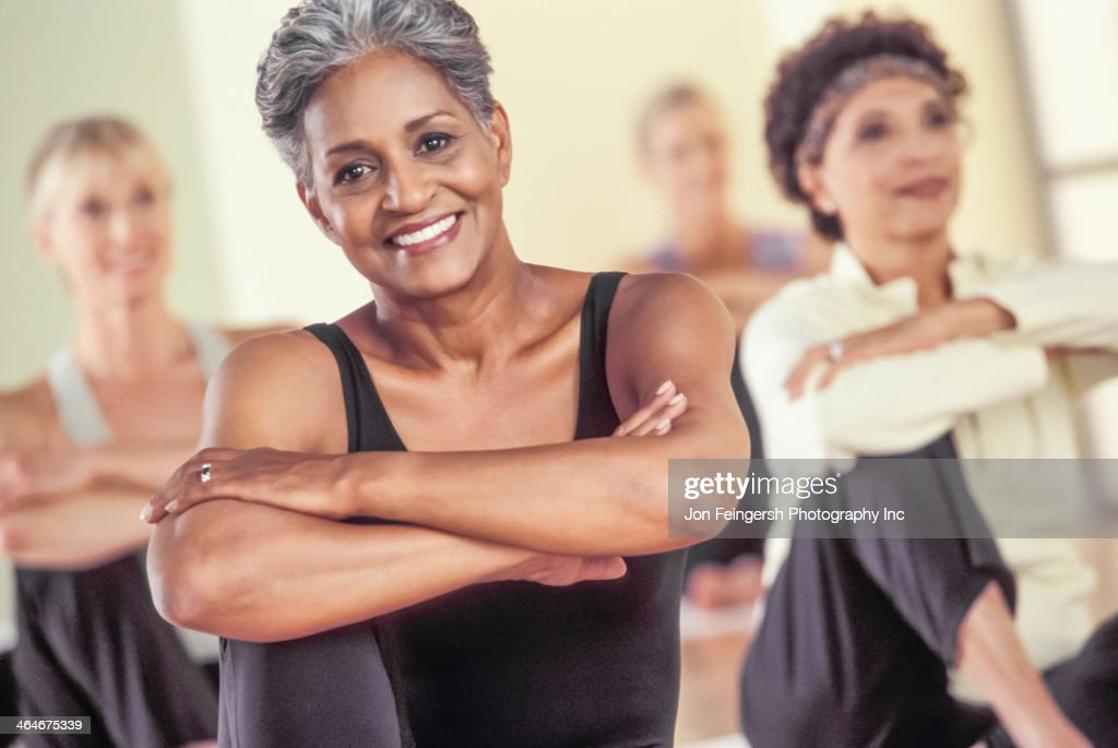 Older women stretching in exercise class : Stock Photo