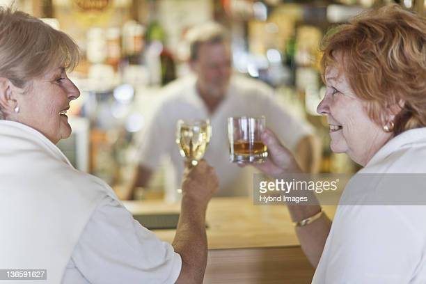 Older women toasting each other at bar