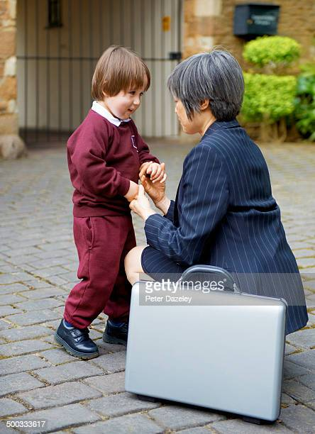 Older working mother at school with son