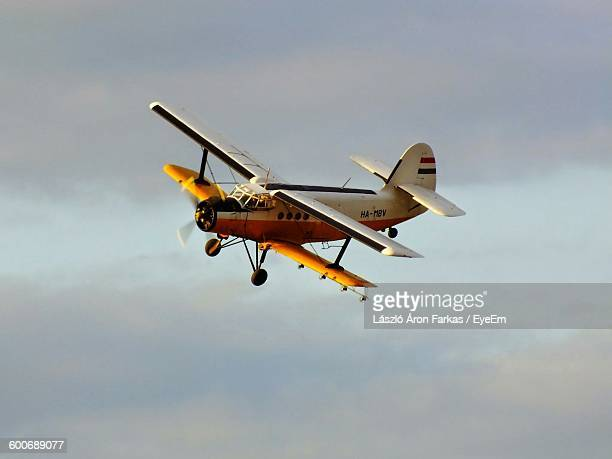 Old-Fashioned Airplane Flying Against Cloudy Sky