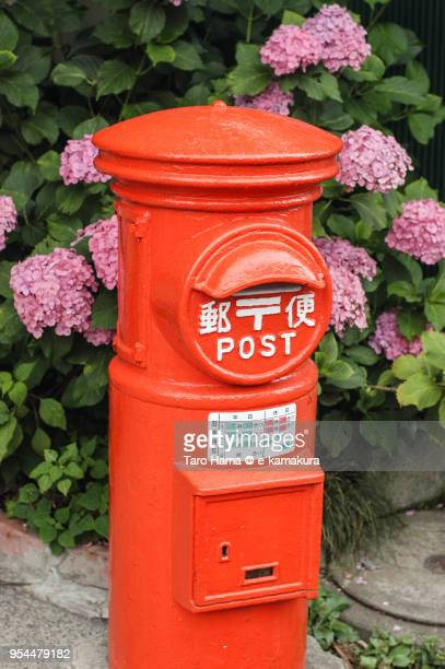 old-fashioned and red-colored post box and hydrangea in japan - e mail stockfoto's en -beelden
