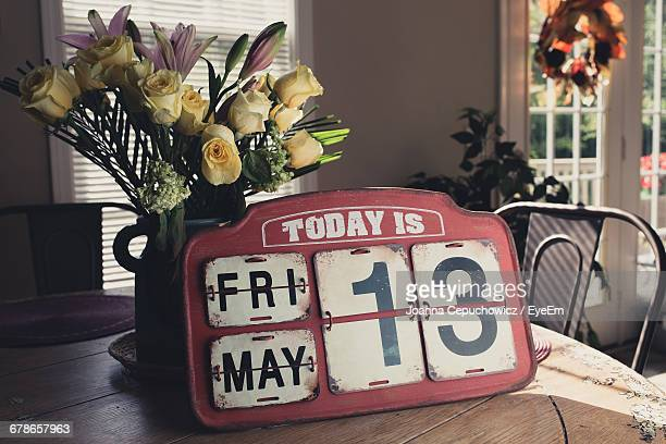 Old-Fashioned Calendar By Flower Vase On Table