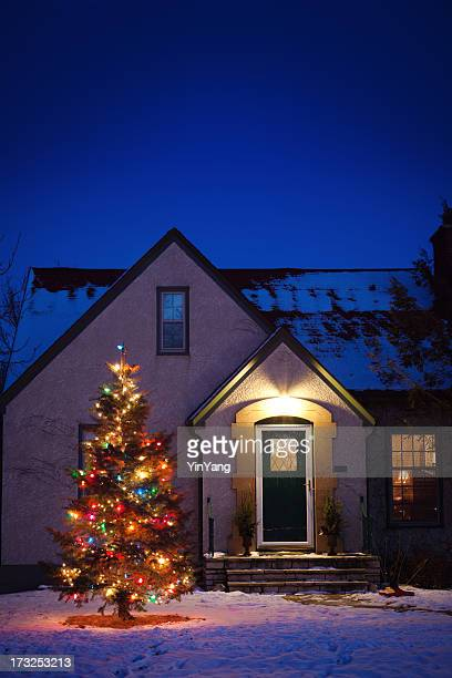 Old-fashioned House with Decorated Christmas Tree Lights in Snowy Yard