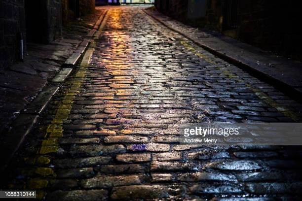 old-fashioned stone paved road at night wet with rain and reflecting street lights, old town, edinburgh - differential focus stock pictures, royalty-free photos & images