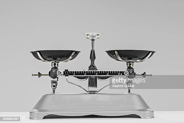 Old-fashioned weighing scale against gray background