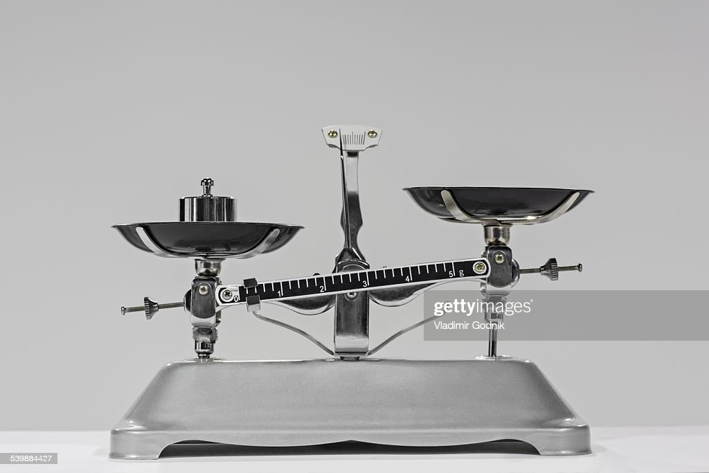 Old-fashioned weight on weighing scale against gray background : Stock Photo