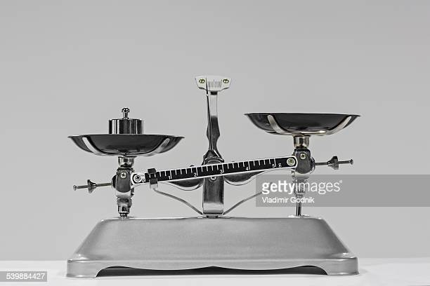 Old-fashioned weight on weighing scale against gray background