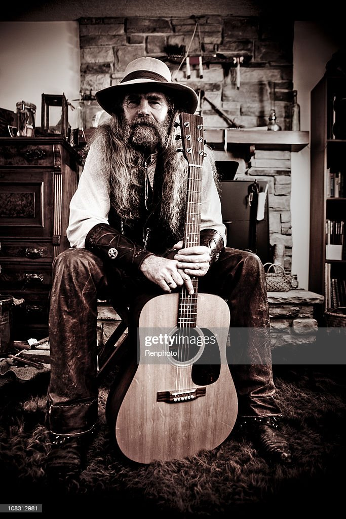 Old-Fashioned Western Cowboy Posing with Guitar : Stock Photo