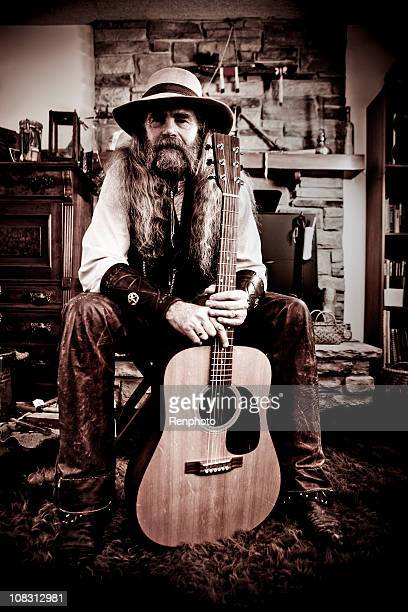 Old-Fashioned Western Cowboy Posing with Guitar