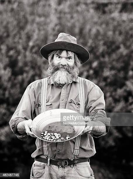 old-fashioned western prospector showing his pan black and white - gold rush stock photos and pictures