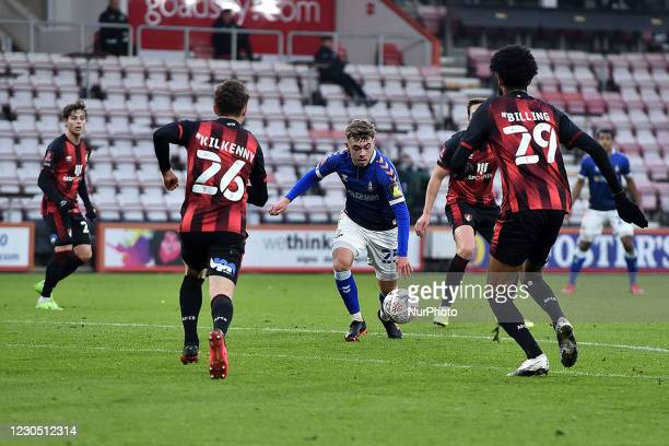 Oldham Athletic's Alfie McCalmont tussles withGavin Kilkenny of Bournemouth and Philip Billing of Bournemouth during the FA Cup match between...