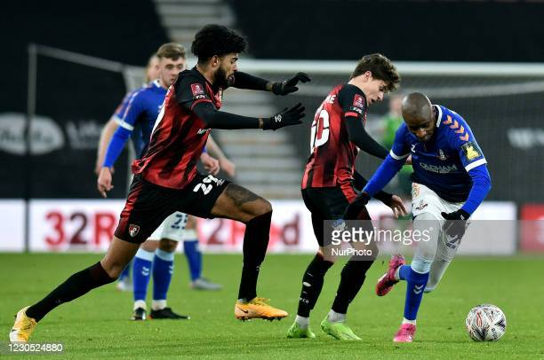 Oldham Athletic's Dylan Bahamboula tussles with Gavin Kilkenny of Bournemouth and Philip Billing of Bournemouth during the FA Cup match between...
