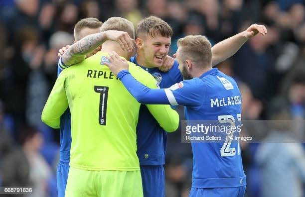 Oldham Athletic's Rob Hunt Connor Ripley and Ryan McLaughlin celebrate after the Sky Bet Championship match at SportsDirectcom Park Oldham