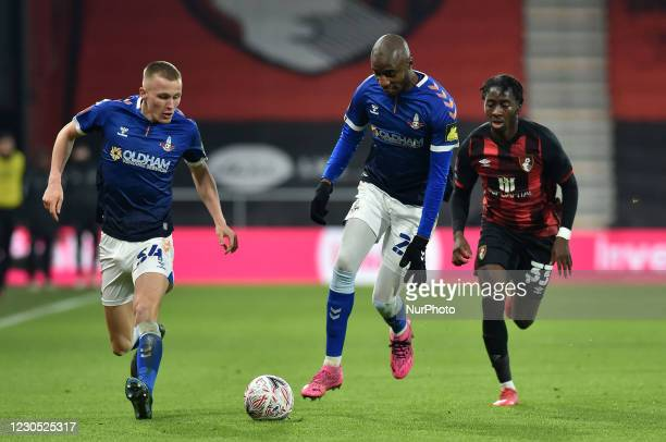 Oldham Athletic's Tom Hamer and Oldham Athletic's Dylan Bahamboula tussles with Jordan Zemura of Bournemouth during the FA Cup match between...