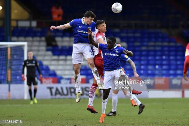 Oldham's George Edmundson and Christopher Missilou and Stevenage's Alex Revell in action during the Sky Bet League 2 match between Oldham Athletic...