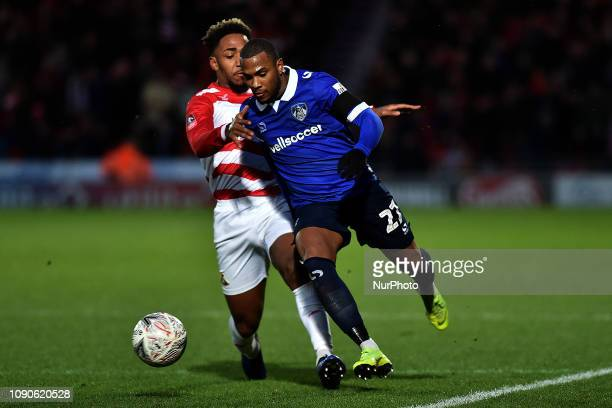 Oldham's Gevaro Nepomuceno and Doncaster's Mallik Wilks during the FA Cup match between Doncaster Rovers and Oldham Athletic at the Keepmoat Stadium,...
