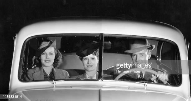 Oldsmobile driver and female passengers. Creator: Unknown.