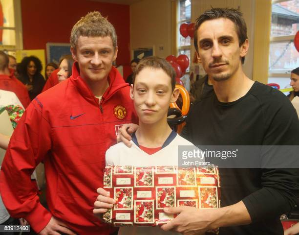 Ole Gunnar Solskjaer and Gary Neville of Manchester United pose with Nathan Statham during the club's annual Christmas hospital visits at Booth Hall...