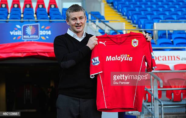 Ole Gunnar Solskjaer holds aloft the club shirt after being unveiled as the new Cardiff City Manager at Cardiff City Stadium on January 2 2014 in...