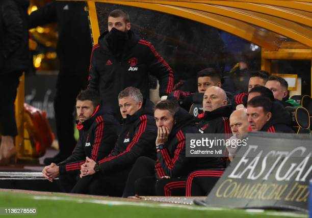 Ole Gunnar Solskjaer interim manager of Manchester United watches the match from the bench alongside Michael Carrick David de Gea Mike Phelan and...